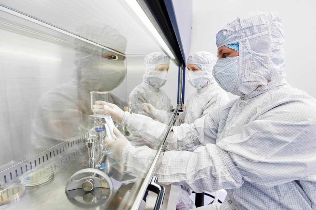 scientists in a lab with protective clothing
