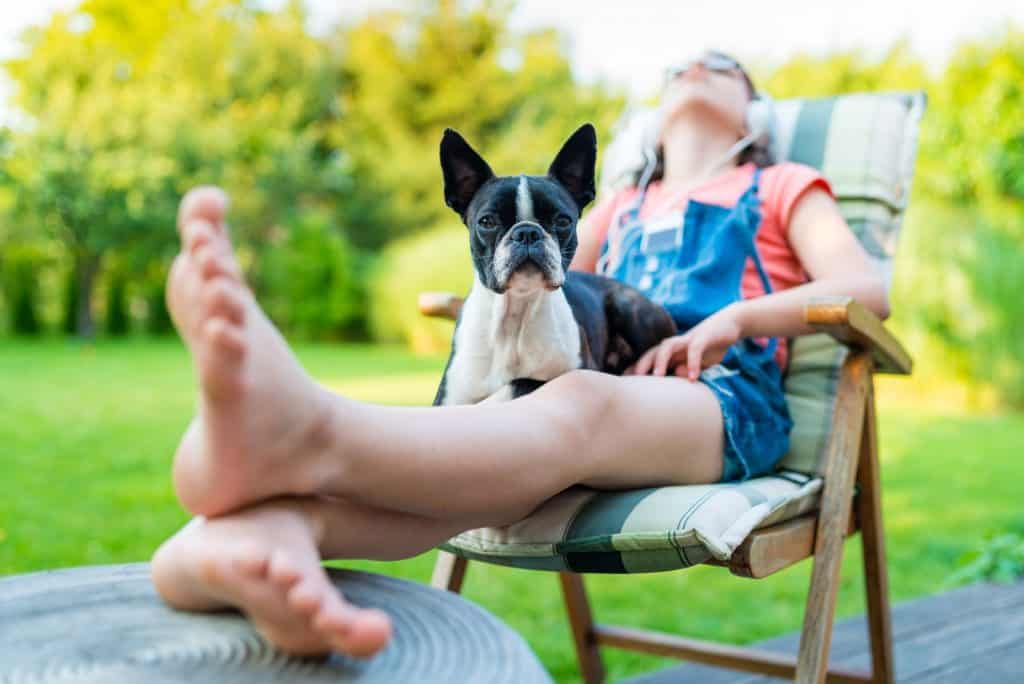 - Dog and teenage girl resting in the garden