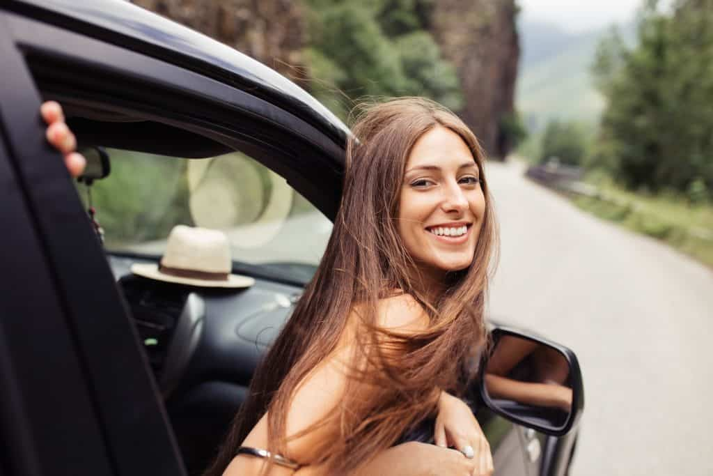 smiling woman hanging head out of car window
