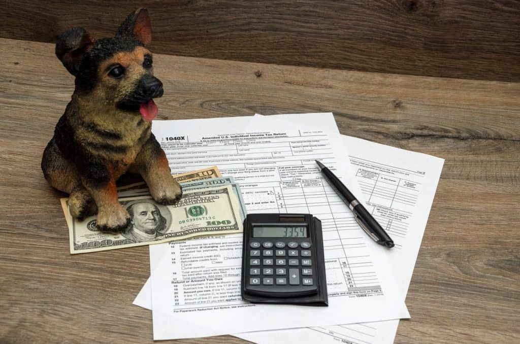 mini statue of a dog being used as apaper weight. On a table with money and a calculator