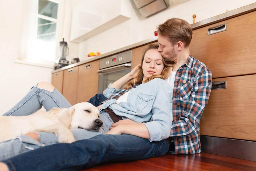 Romantic young couple sitting on the kitchen floor next to their dog