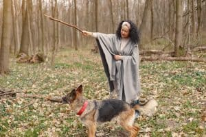 Photo of Woman Training Her Dog With a Stick