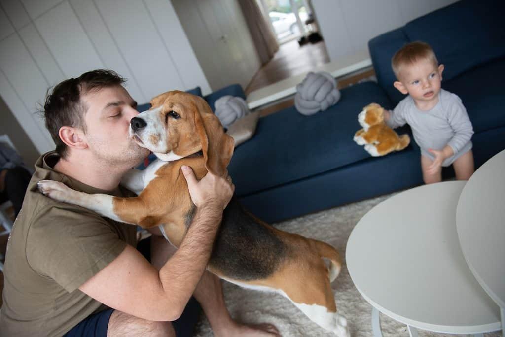 man plafylly kissing his dog